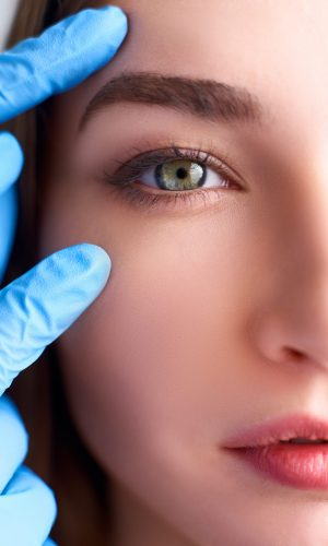 Beautician doctor hands in gloves touching female face. Upper eyelid reduction, double eye lid removal plastic surgery concept. Ophthalmologist or oculist checks healthy vision in green eyesight.